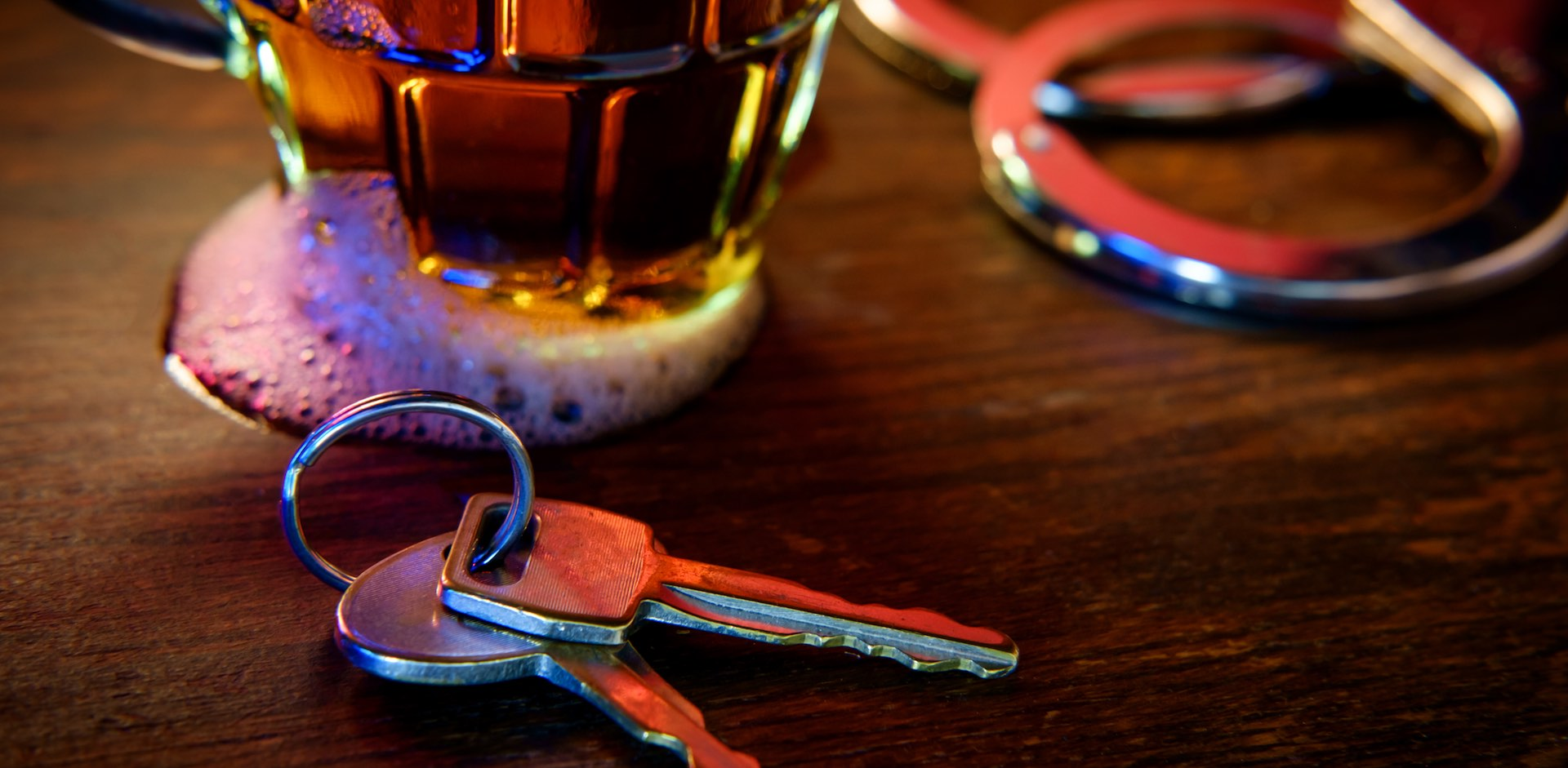 Driving while under the influence after Third DWI Offense resulted in keys on table with booze and handcuffs.