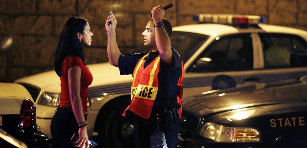 Police officer performs field sobriety test on women.